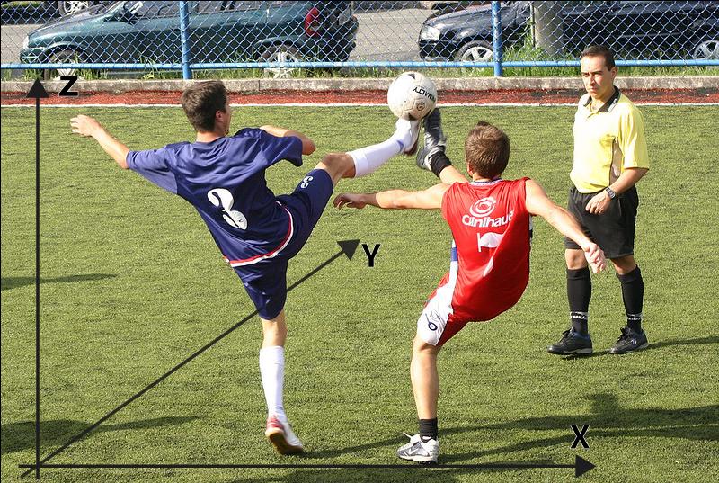 Jogadores de futebol disputando bola que se encontra no ar.
